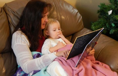 Grandma with a little girl reading a book while she sucks on her fingers
