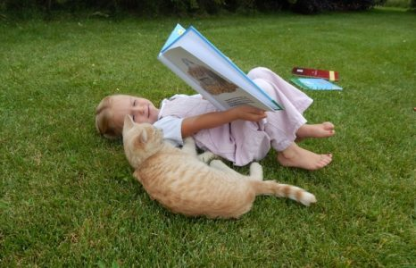 Little girl reading a book to her cat laying on the grass