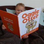 Blonde headed girl reading Oggie the Otter children's book