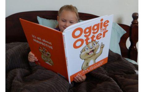 Blonde headed girl reading Oggie the Otter children's book