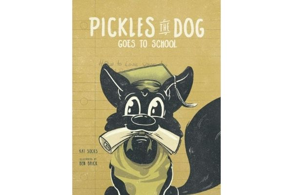 "Pickles the dog goes to school. Cover of the book ""Pickles the dog goes to school"" yellowish/green cover with a black dog and a graduation hat and papers in his mouth."